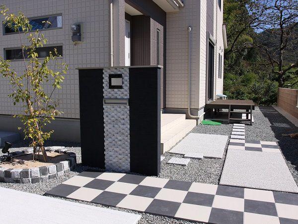 外壁のチェックパネルに合せて、四角形で遊んだ玄関アプローチ。