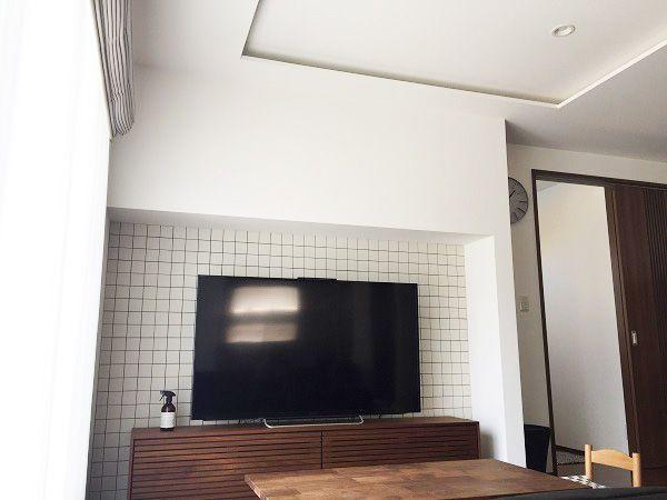天井を折上げ天井にすることにより一層天井が高くなり、ゆったりとした空間となりました。折上げ天井には間接照明が入り、夜はホテルライクなラグジュアリー空間を演出。TVコーナーはご主人様のこだわりで、奥の壁面にはタイルを貼り、印象的な仕上がりとなりました。南側の大開口からは反対側にあるキッチンまで日の光が差し込み、明るいリビングとなりました。