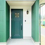 外壁色に合わせ、玄関ドアもグリーンに。