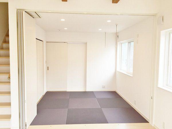 こちらは玄関から上がってすぐに入れる和室です。畳はブラック、照明はダウンライトにし、モダンな和室になりました。