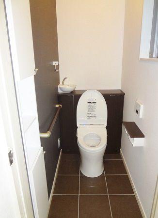 トイレはタンクレスで背面収納。カウンター上の手洗器が可愛いです。