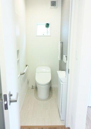 1階トイレはタンクレス風のトイレを採用しました。トイレ、手洗器、手摺は白で統一していますが、一部のクロスの色を変更しています。敢えて濃いグレーを設ける事で白い手洗器とお客様がご自分で購入されたペーパーホルダーとタオルリングが映えるようになってます。2階トイレは明るいブルーを採用しました。これもまたトイレの白さとマッチして、清潔感がありながらもちょっとした遊びを含んだ空間に仕上がりました。