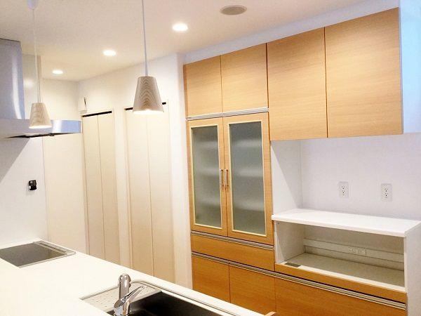 右から、造作のカップボード、パントリー、掃除機等の収納です。 収納スペースは存在感をなくすため白い建具にしてあります。 キッチンとカップボードの色は他と合わせて木目柄。マット調を選びました。