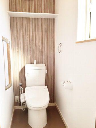 2階のトイレは木目調のアクセントクロスを使用し、飽きのこないデザインに。