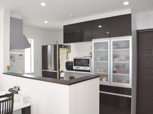 ダーク木目調のキッチンと、カップボードが空間を引き締めています。キッチン横にはパントリーとミニ収納スペースがあり、奥様にうれしい造りとなってます。