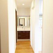 玄関ホールからLDKへの扉は2つあります。一つは開けるとスリット階段が出迎えてくれる扉。そしてもう一つの扉を開けると見えるのがこの光景です。すぐ左にはトイレ、突き当りにある洗面台の左には脱衣場があります。この廊下はキッチンの回遊の途中でもあるので、帰宅時のキッチン、脱衣場、トイレへのアクセスもスムーズです。一般的には脱衣室にある洗面台が廊下に出してあることで、誰かがお風呂に入っていたり、お客さんが手を洗いたいといわれたりした場合でも気兼ねなく洗面台を使って頂くことができます。