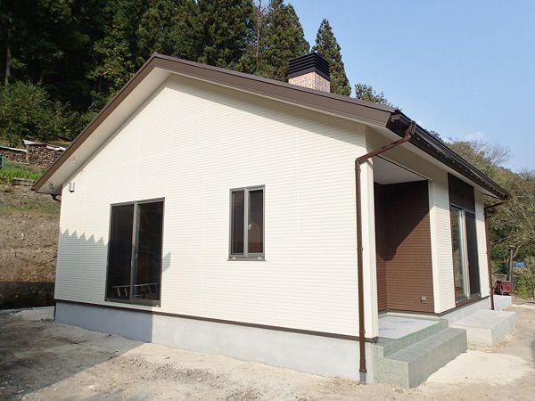 白と茶色のツートンカラーの外壁がナチュラルで、屋根の上から覗く煙突が暖かさを思わせる外観です。
