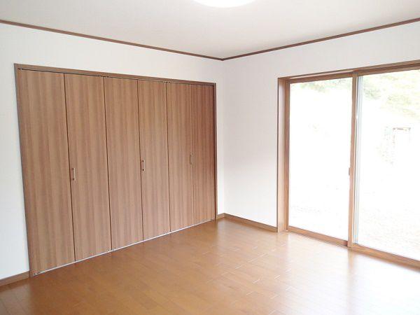 落ち着いたダークカラーのフローリングと白い壁が、ほっこりと温かくなるような広々とした8畳ある寝室です。