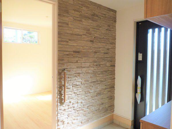 柔らかい配色の玄関はすっきりとした清潔感と石の装飾が重厚感を演出。床から天井までの石の壁はベージュベースの配色で温かみを保ち、柔らかい印象。