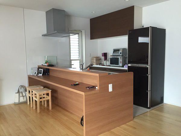 対面式に配置したキッチンにはローテーブルのユニットを搭載し、キッチンとダイニングを一体化!ダイニングテーブルはあえて置かず、空間はコンパクトに、キッチンは広々と!