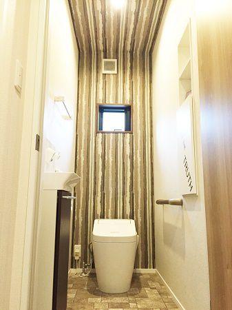 壁紙を使い、個性的なトイレに仕上がりました。特にトイレの奥に縦ラインの壁紙を天井から張ることによって広さと奥行き間をつくりました