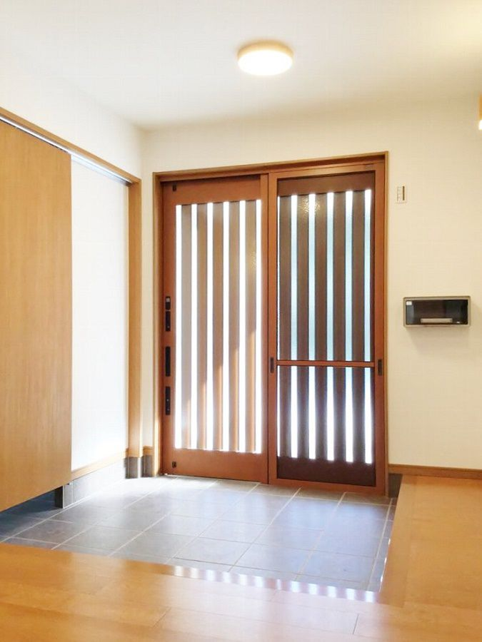 格子の玄関扉から日の光が入る、広々とした玄関ホールです。