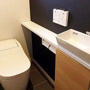 トイレはタンクレス。手洗いをつけ、さりげない波模様のクロスと キラキラ光るブラックのアクセントクロスでお店のような空間に。