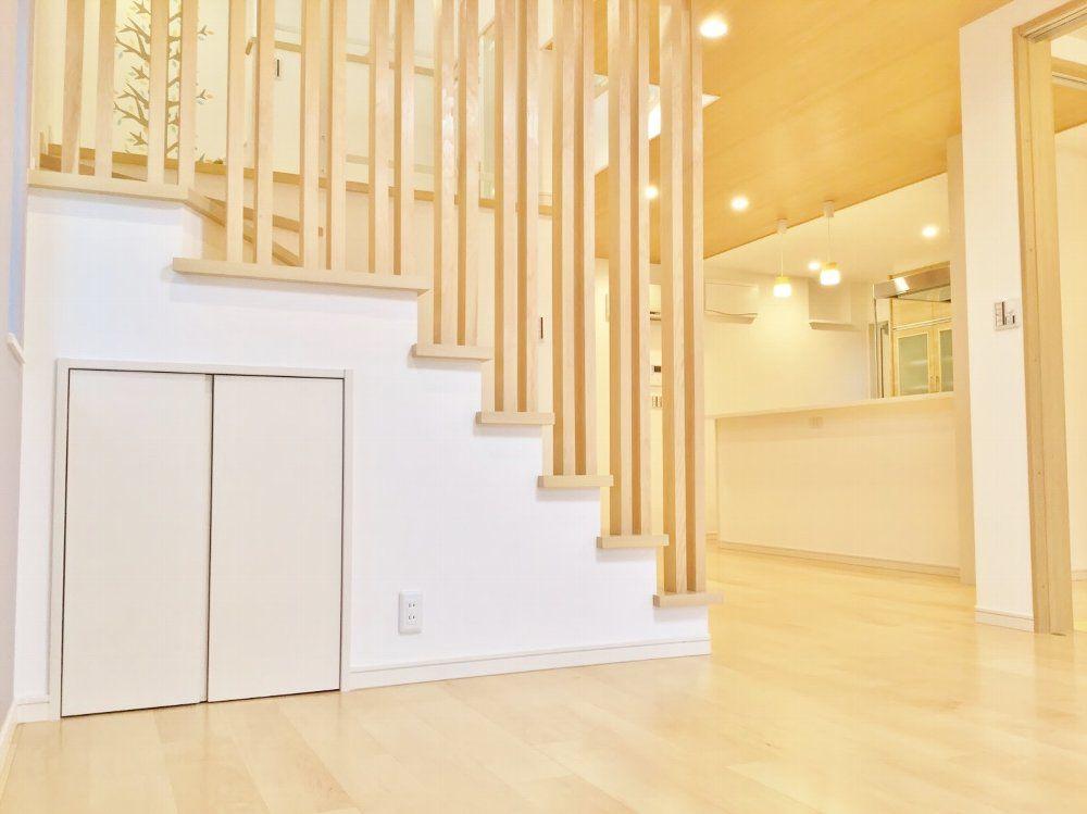 階段には木の格子を造作し、おしゃれなアクセントに。 空間を広く見せるのにも役立っています。 階段下のわずかな空間も座布団などしまって置くのに便利な収納にしました。