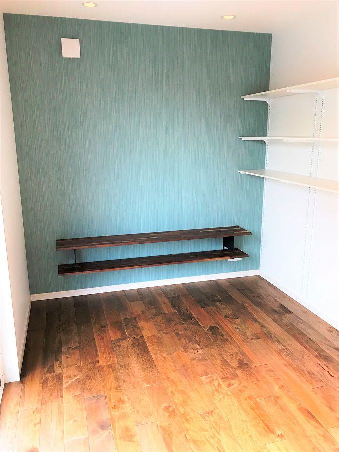 奥の壁紙の色を替え少し落ち着いた空間がつくられます。TVボードにも木材を使用しています。