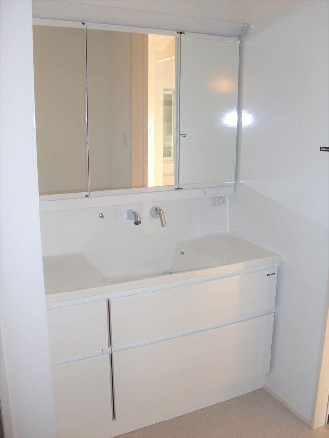 壁いっぱいの洗面化粧台の側面はホーローパネル。小物を張り付けたりと意外と便利。