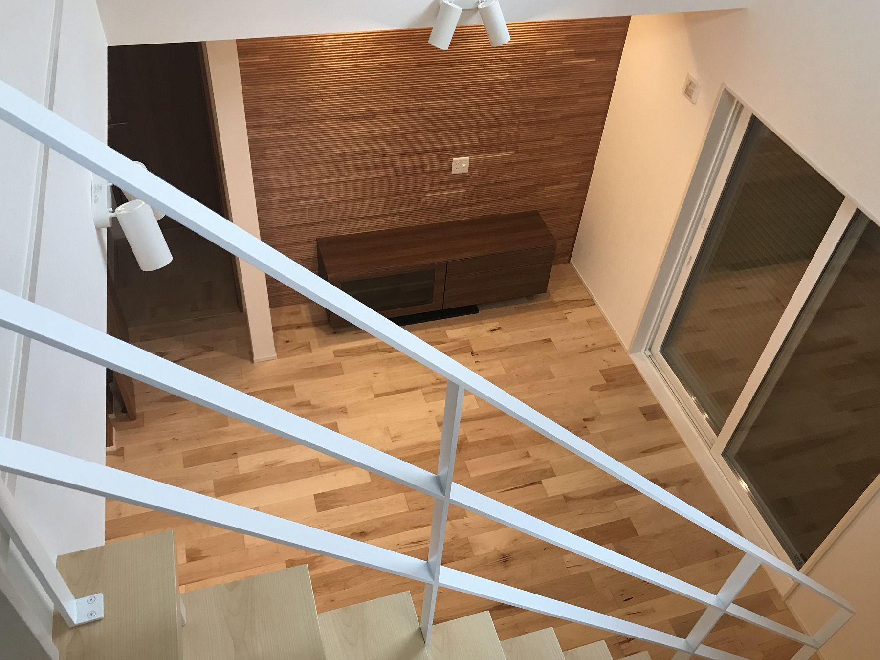 無垢のフローリングが暖かみのある雰囲気を演出してくれるリビング。大きな吹き抜けとオープン階段とのつながりもオシャレな空間を助長してくれます。
