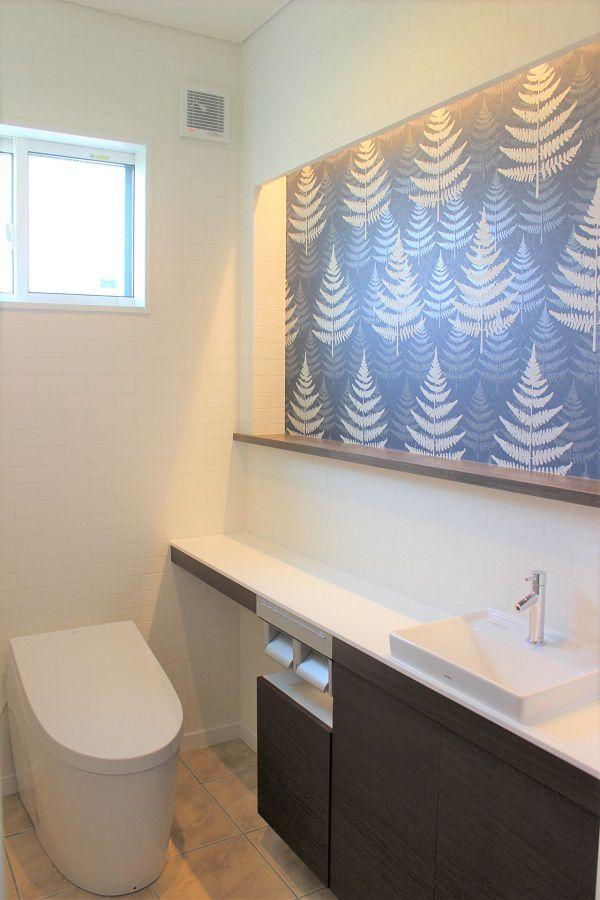 トイレを落ち着きのある空間にするということで間接照明を用い、ニッチの壁紙にアクセントをつけました。