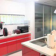 収納スペースを充実させたいという奥様の拘りから、食器棚とは別に乳白色の格好いい扉で隠したカップボードがあります。沢山のものを収納できてキッチンは常にすっきりできます。そしてキッチンの色はご主人の好きな赤をセレクトされています。