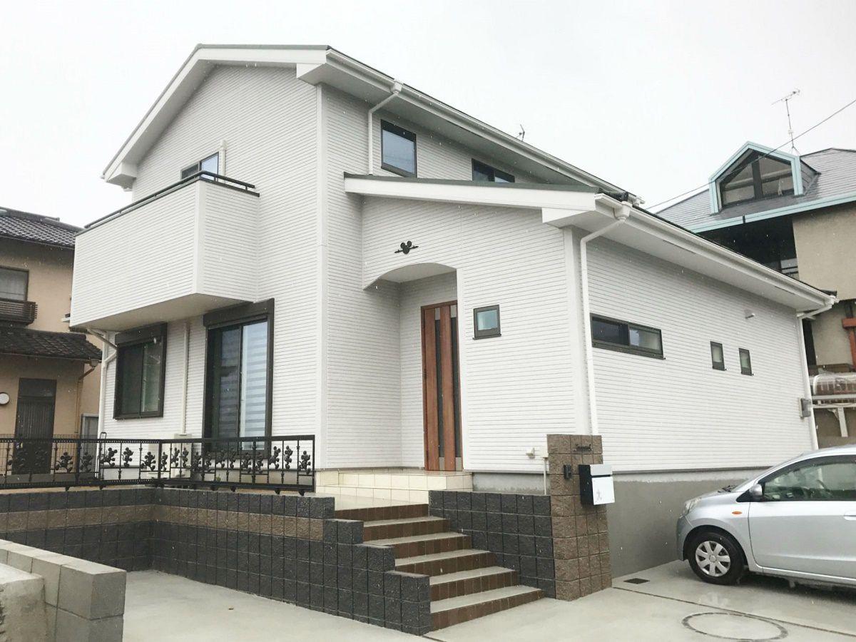 サッシを茶色、外壁を白、屋根を緑にして全体的にフェミニンな仕上りになりました。玄関部分はアーチ状に加工し、その上に壁飾りを付けています。
