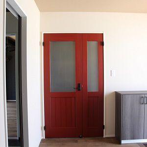 リビングドアをカラーペイントの無垢ドアに。親子ドアで見た目も広々。
