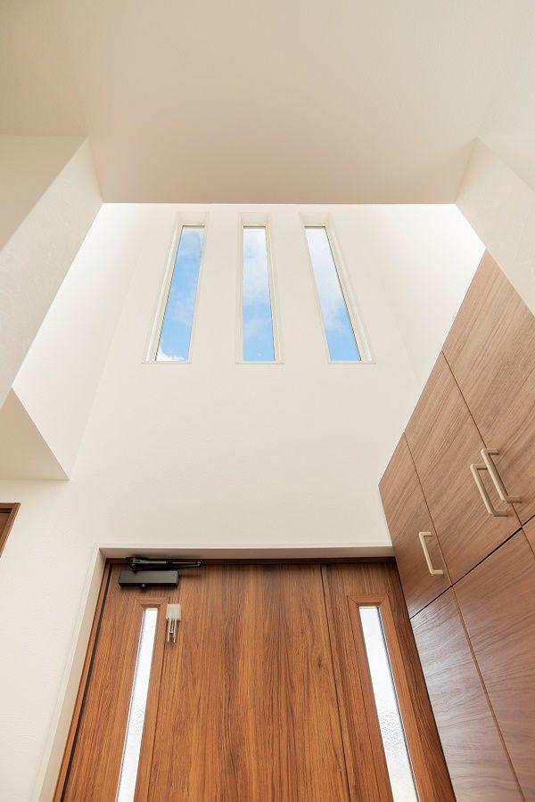 吹抜け上部に設けられた窓から射し込む、明るい光に満ちた玄関ホール。