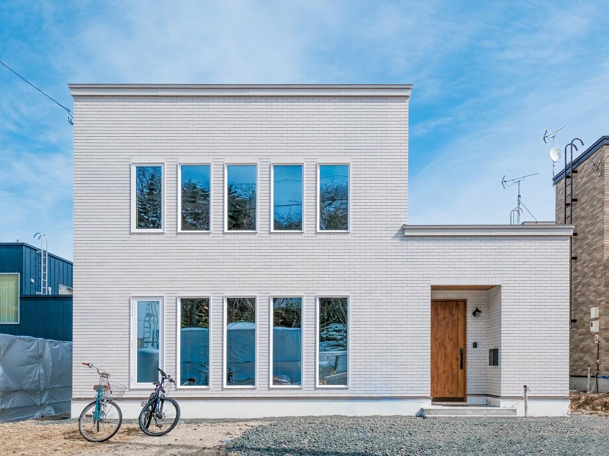 タイルの白は長い時間を経ても変わることなく美しい。窓のデザインが建物の価値を高めてくれるシンプルデザイン。