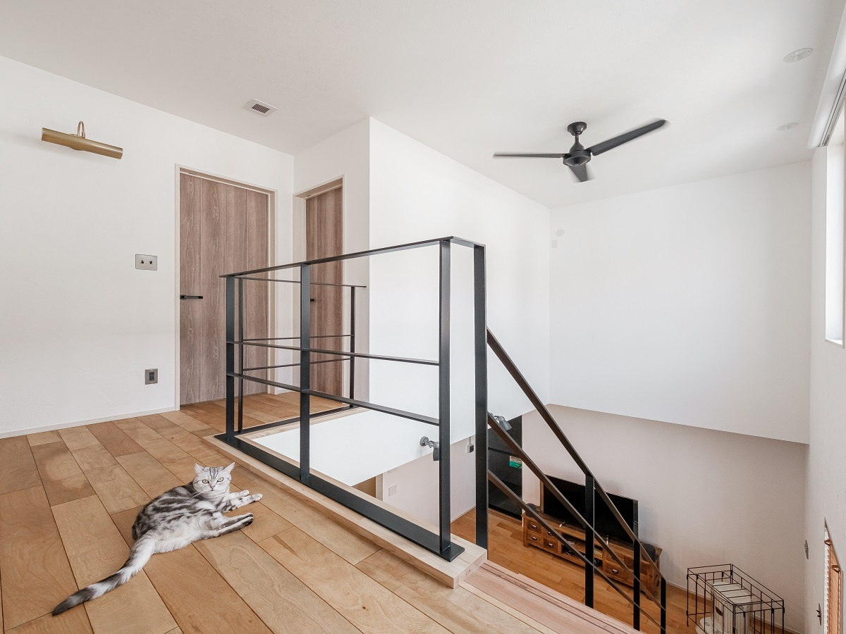 スチール階段から続くホール手摺も華奢な黒のスチールが無骨でかっこいい。2階床にも無垢フロアを使うことでより無骨な手摺と対極にある床の温かみを感じることができる。