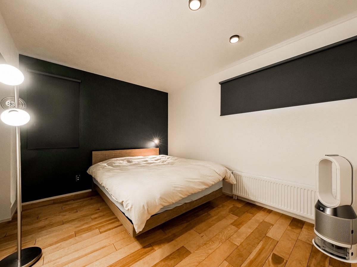 寝室には落ち着きのあるダークトーンのアクセントウォールでしっとりした空間。照明器具を最小限度にすることで、必要な場所だけが照らせるように、また良い眠りへ導いてくれるような工夫。