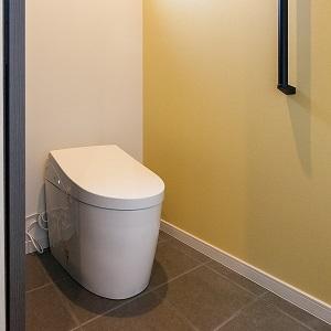 トイレの床はタイル仕様でお掃除のしやすさがポイント。アクセントウォールは黄色系で明るく温かみのある印象