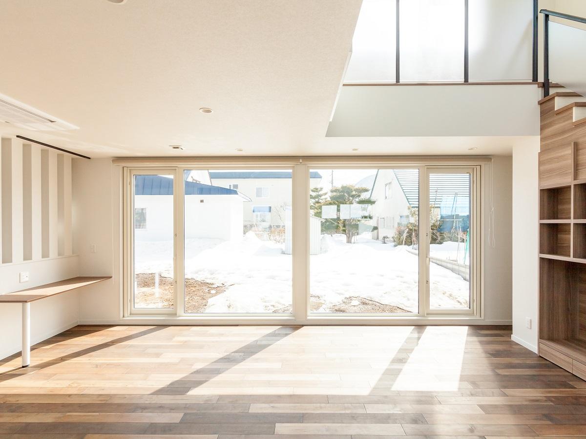 リビングにはくつろぎを求めて。大きな窓、大きな吹抜けは無垢フロアを優しく照らす。風の通りも良くなる様、窓のレイアウトも考慮。階段にはTVボードと収納を兼ねたこだわりの造作収納を設置。家族が過ごすのに快適な空間
