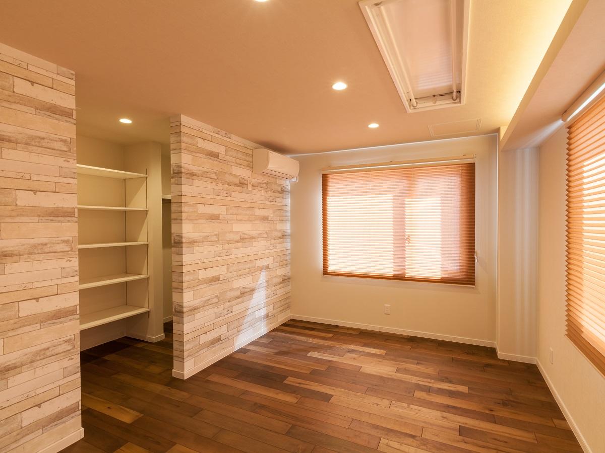 アクセントウォール、プリーツスクリーンのコーディネートが優しい印象の寝室