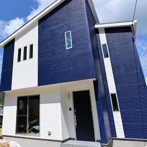 青空にブルーが映える家