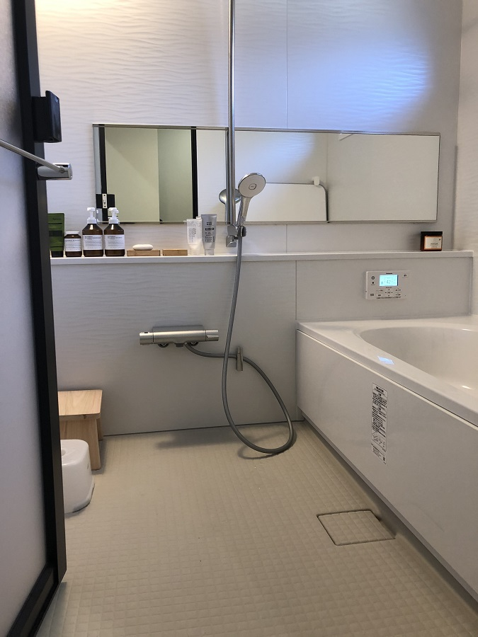 ウェーブラインのアクセントパネルが映える、真っ白で爽やかな浴室。