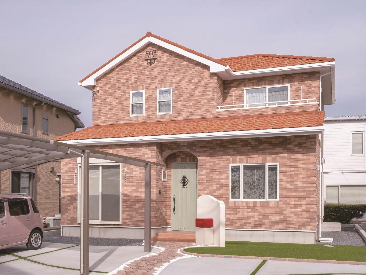 オレンジの瓦にレンガ調のタイルが調和した外観。曲線のアプローチ、赤いポストが素敵