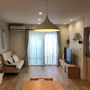 無垢床を採用した明るく柔らかな雰囲気のリビング。その中でも、テレビボード裏に貼られたエコカラットがアクセントとなっています。奥様のお気に入りポイントは床から咲いているように見えるお花のカーテンレース。無垢床と家具の相性も抜群です!ピアノもリビングに置き、ご家族それぞれがお家時間をゆったりくつろげるリビング空間となりました。