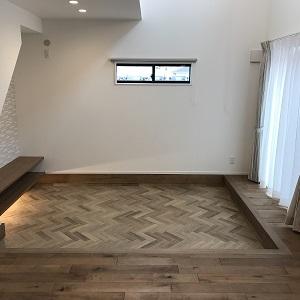 床は矢羽根状のヘリンボーン貼りという貼り方でかっこいいイメージ に  階段下を利用したテレビボードもあります