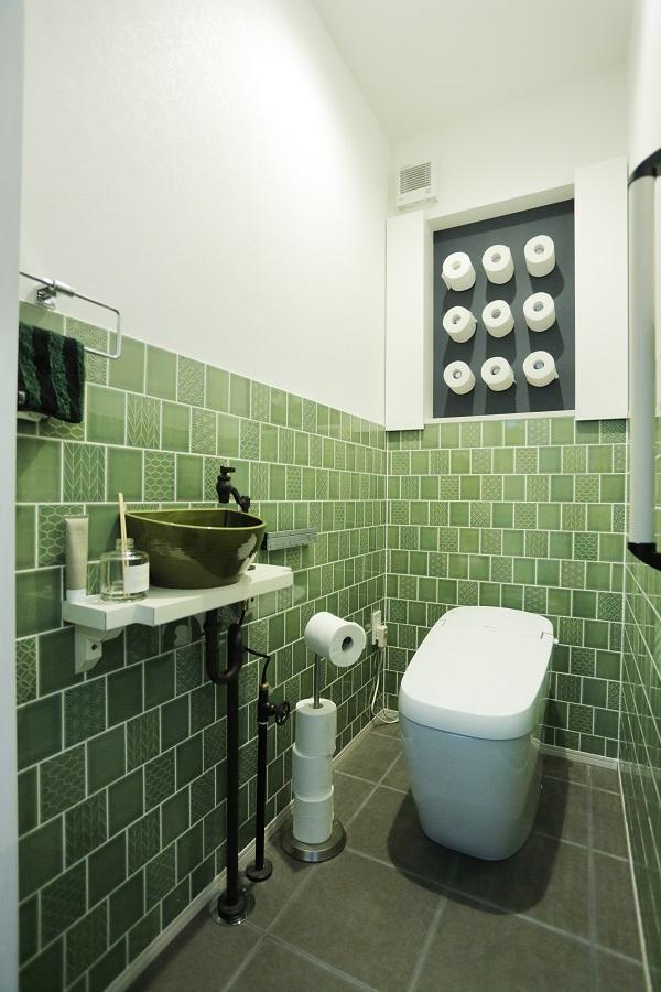 トイレの壁面にはトイレットペーパーをあえて見せる収納を付けました。 全体はレトロな雰囲気でまとまっています。
