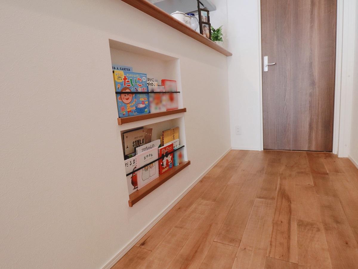 キッチンの反対側の壁にお子様の絵本を収納するニッチ式の本棚。お子様の目線で出し入れ出来て、見せる本棚です。