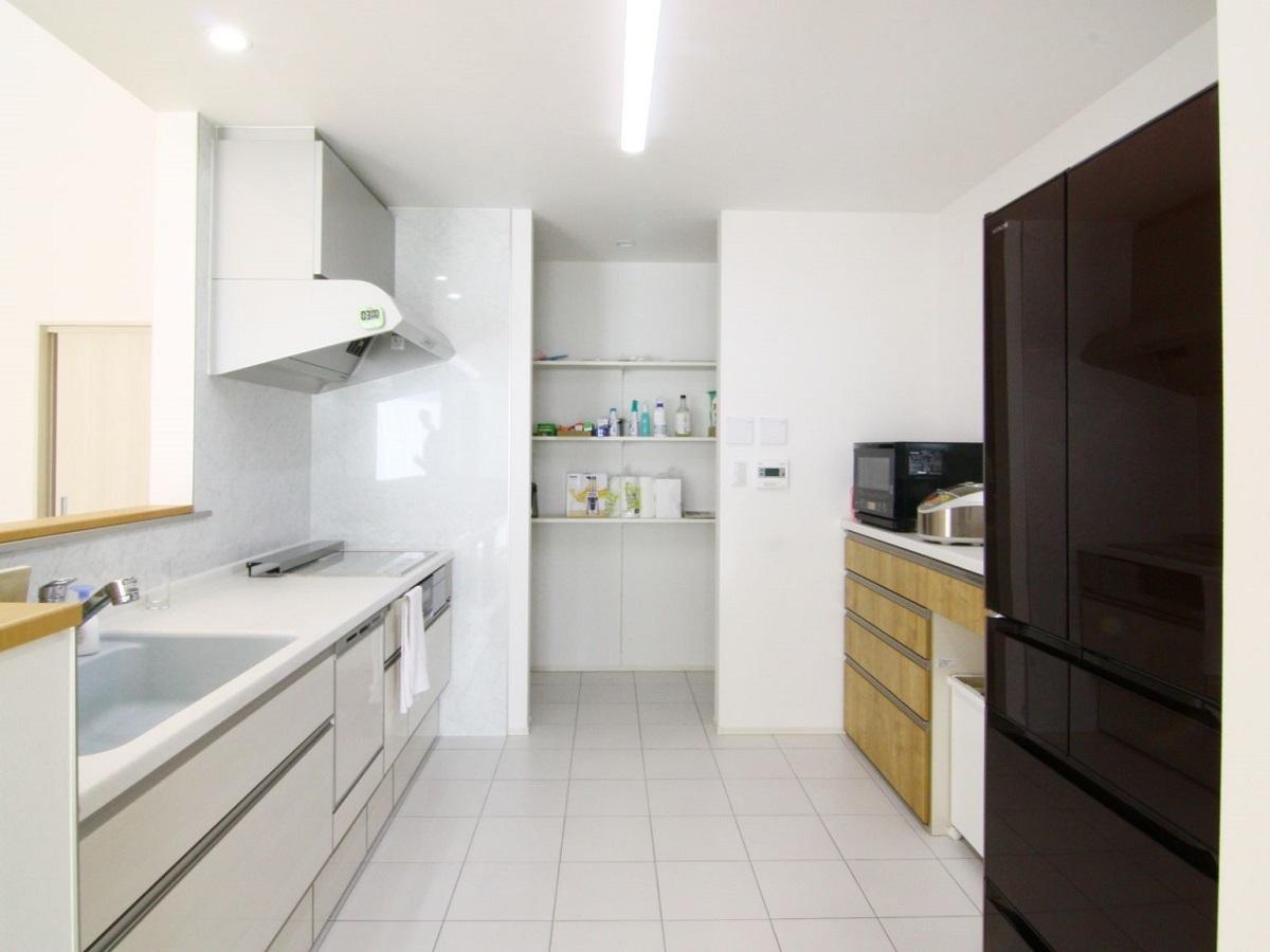 幅・奥行共にゆったりとしたキッチンスペース。床材はタイルにしてお掃除ラクラク。色味はホワイトで統一して清潔感もあります。また冬場でも床暖房のおかげで暖かく快適です。