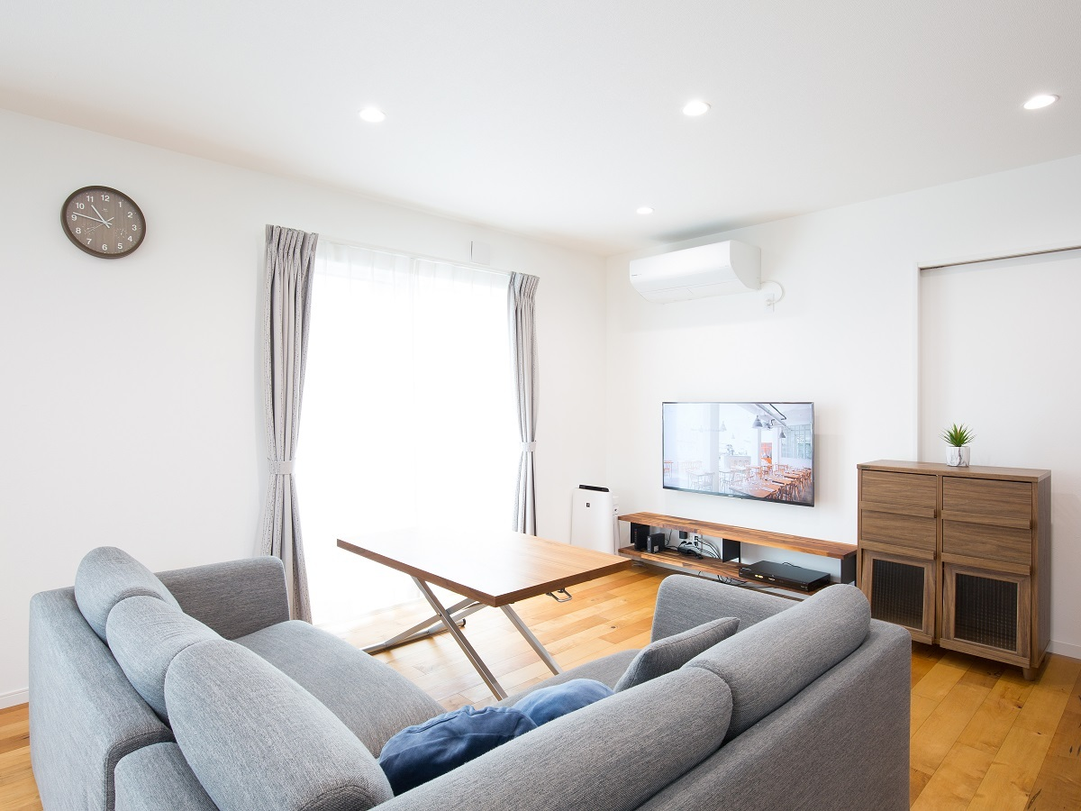 無垢床材とマッチしたグレー色のソファとカーテン、オーク材のチェストとTVボード。居心地の良い空間になってます。